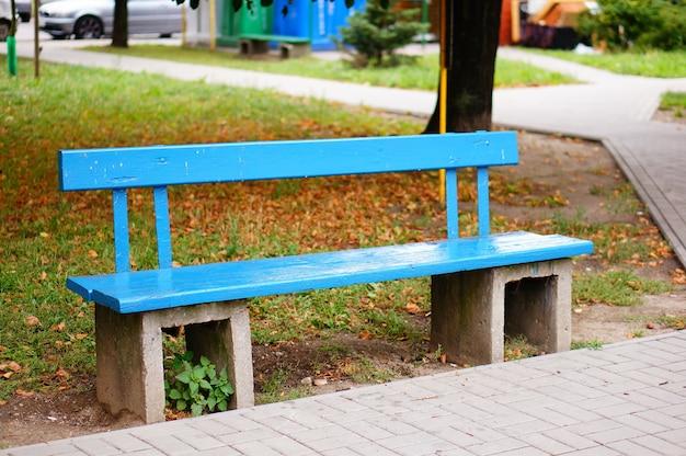 秋の公園の青い木製のベンチ