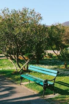 공원에서 금속 패턴과 푸른 나무 벤치