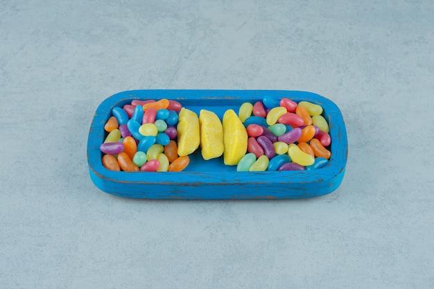 Una tavola di legno blu di caramelle da masticare a forma di banana con caramelle colorate di fagioli