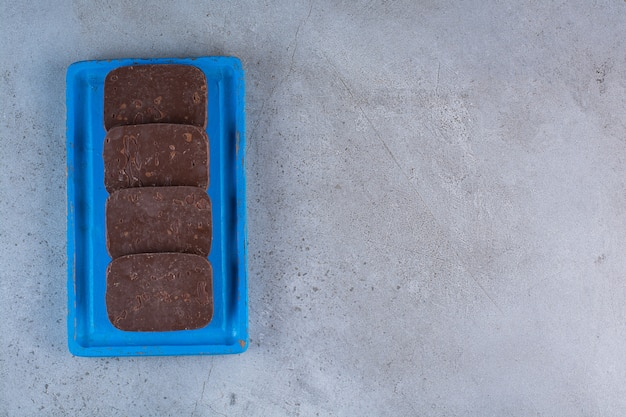 A blue wooden board of chocolate cookies on gray background