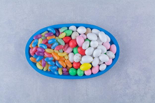 Una tavola di legno blu di caramelle colorate di fagioli di gelatina dolce