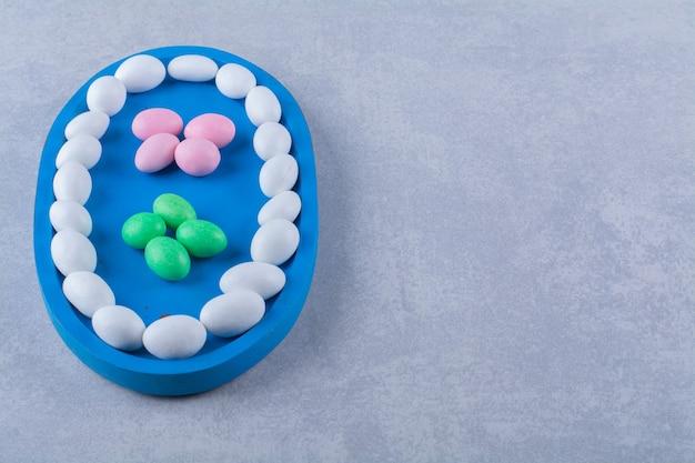 Una tavola di legno blu piena di caramelle colorate di fagioli di gelatina dolce.