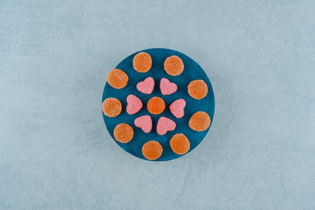 A blue wooden board full of orange sugary jelly candies with heart shaped jelly sweets