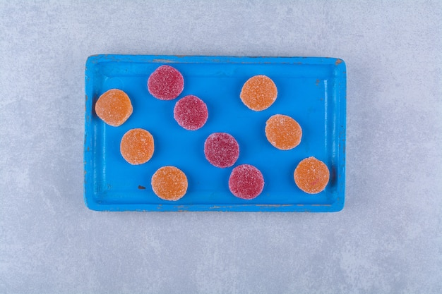 A blue wooden board full of red and orange sugary marmalades . high quality photo