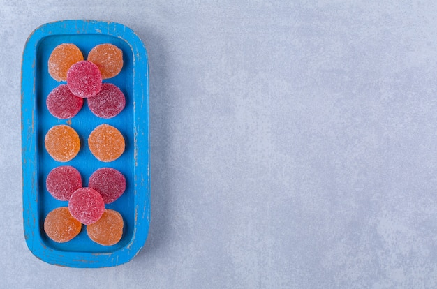 Una tavola di legno blu piena di marmellate zuccherate rosse e arancioni.