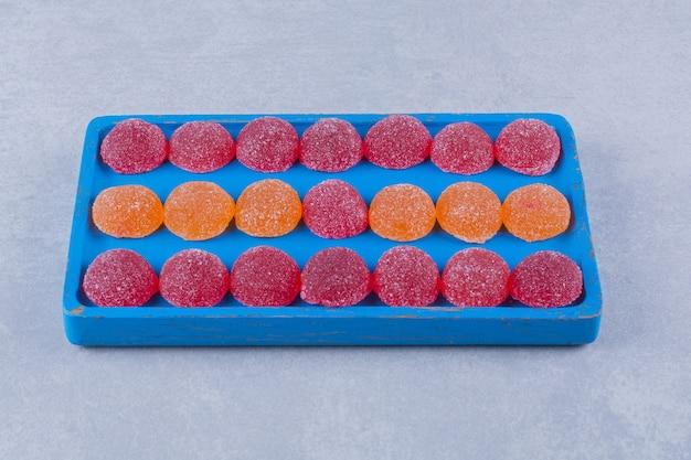 Una tavola di legno blu piena di marmellate zuccherate rosse e arancioni