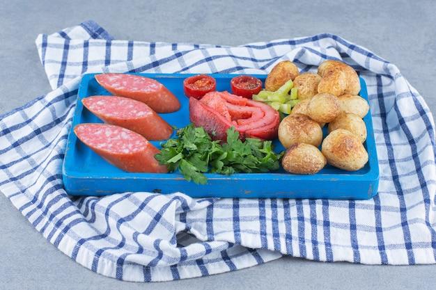 Tavola di legno blu piena di snack. su sfondo grigio.