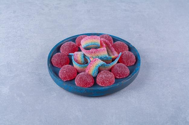 Una tavola di legno blu di caramelle di gelatina rosse zuccherate con dolce liquirizia arcobaleno. foto di alta qualità