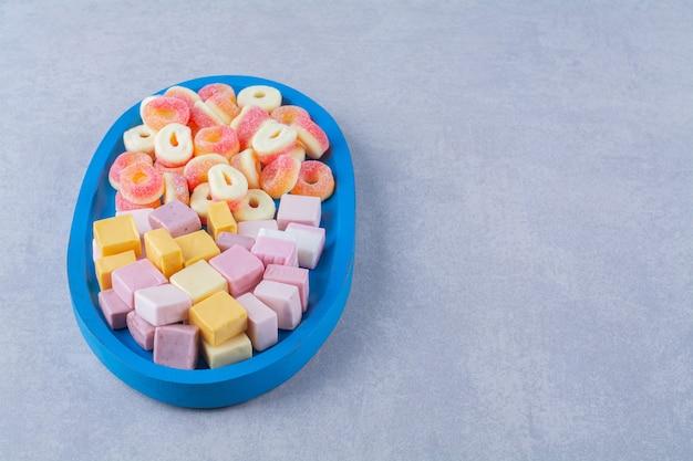 Una tavola di legno blu di caramelle di gelatina rosse zuccherate con dolce liquirizia arcobaleno.
