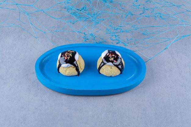 Una tavola di legno blu di biscotto dolce con sciroppo di cioccolato e granelli colorati.