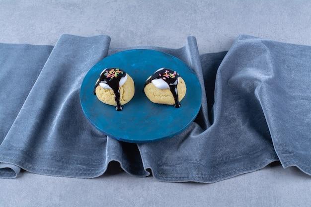 Una tavola di legno blu di biscotti dolci con sciroppo di cioccolato e granelli colorati.