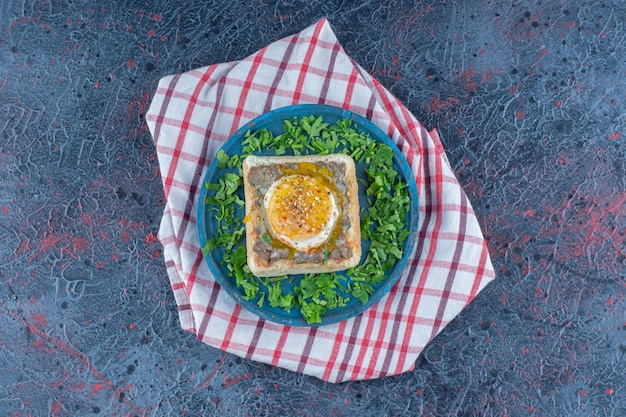 Una tavola di legno blu di pane tostato con uova ed erbe aromatiche.