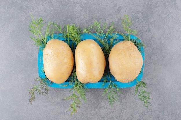 Una tavola di legno blu di patate crude con aneto fresco