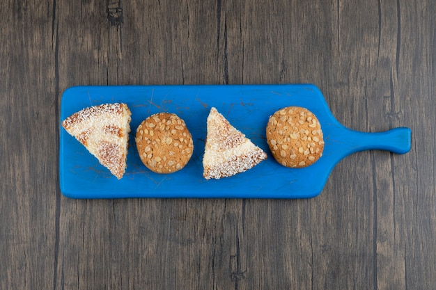 A blue wooden board with oatmeal cookies and pieces of cake .