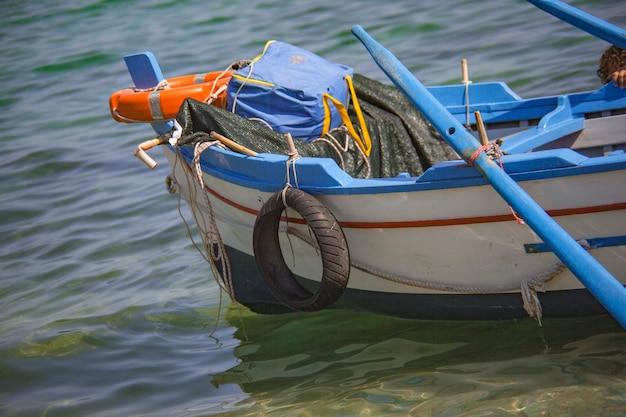 Синяя деревянная деталь лодки в прозрачном море
