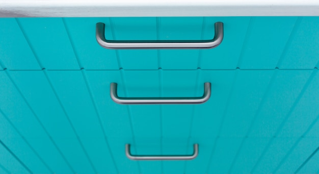 Blue wooden facade of kitchen cabinets made of thin strips with chrome handles.
