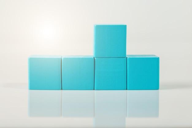 흰 벽에 고립 된 푸른 나무 도형 큐브