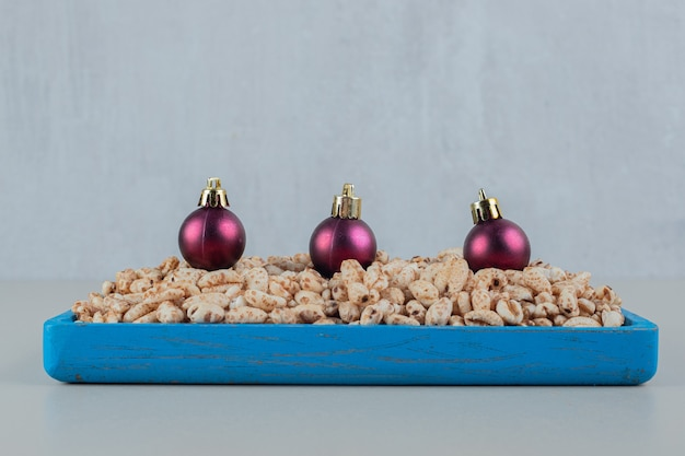 A blue wooden plate full of healthy cereals with christmas balls .