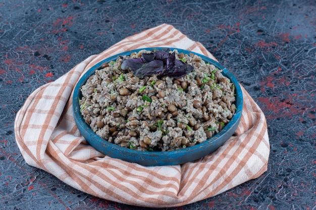 Un piatto di carne macinata in legno blu con piselli ed erbe aromatiche