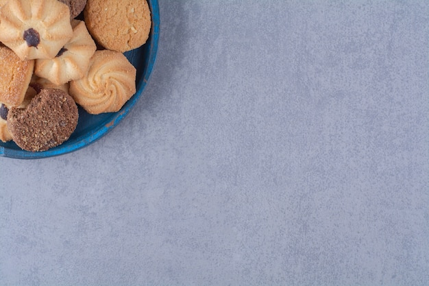 A blue wooden plate with sweet different cookies .