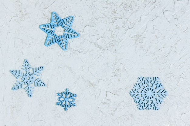 Blue wooden snowflakes on light background