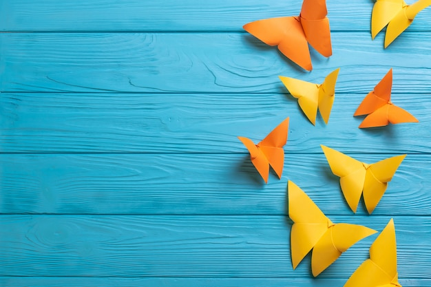 Blue wooden surface with colorful paper origami butterflies with copy space for your text