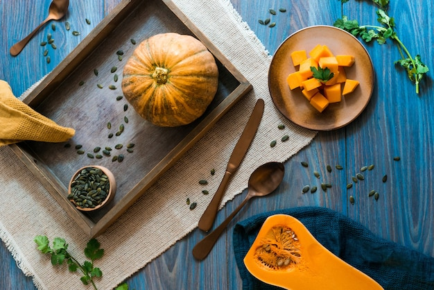 A blue wooden table with orange pumpkins in all forms on top