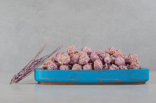 Blue wooden tray filled with popcorn candy and a purple stalk of wheat on marble background.