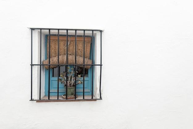 Синее деревянное винтажное окно с железными решетками и льняной занавеской на белой стене.