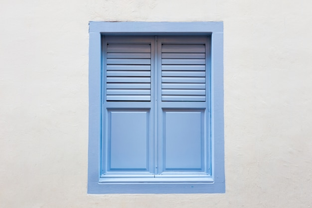 Синее деревянное окно - классический старинный стиль на белом фоне стены из цемента.