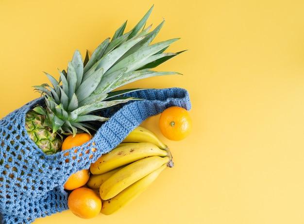 노란색 배경에 여러 과일이 있는 파란색 짠 쇼핑백. 공간을 복사합니다.