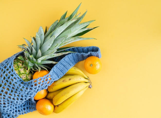 Blue woven shopping bag with assorted fruits on yellow background. copy space.