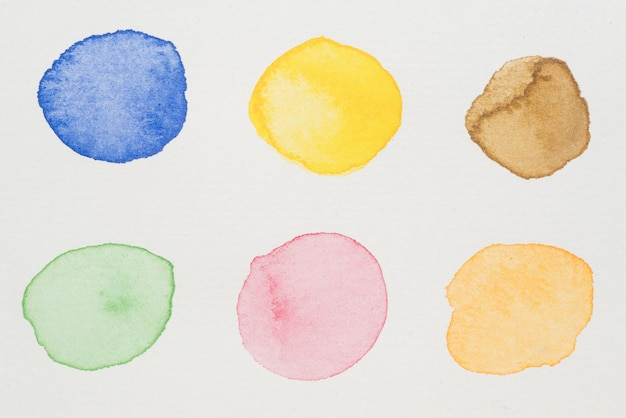 Blue, yellow, brown, green, pink and orange paints on white paper