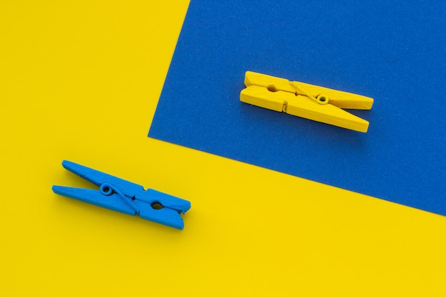 Blue and yellow clothespins on the background
