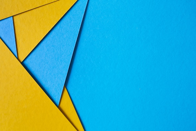 Blue and yellow, color paper geometric flat lay background.