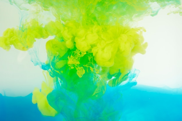 Blue and yellow paint mixing in water