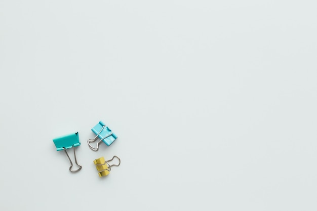 Blue and yellow paper clips on white background. work and education concept.