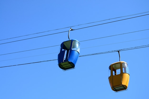 Blue and yellow passenger cable way cabins in the clear sky