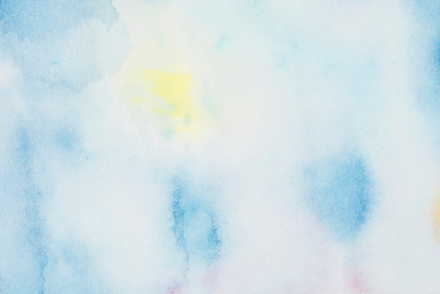 Blue and yellow spots of paints on white paper