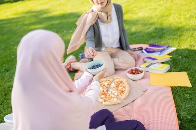 공부 후 블루 베리. 외부 친구와 함께 공부 한 후 블루 베리를 복용하는 히잡 여성