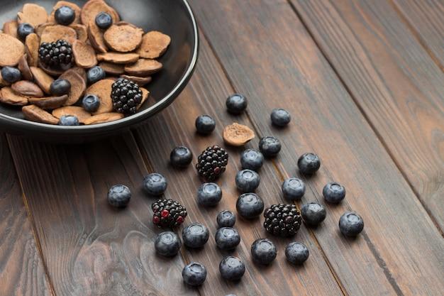 블루 베리와 블랙 베리 테이블에. 블랙 세라믹 그릇에 초콜릿 팬케이크와 딸기. 어두운 목재 표면. 평면도. 공간 복사