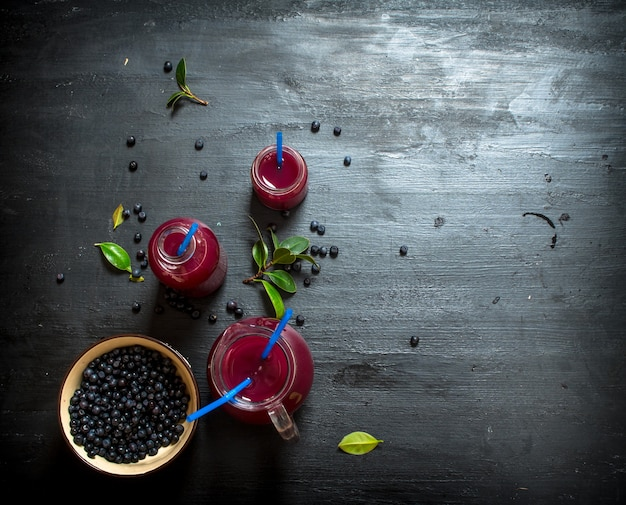 ブルーベリーとブルーベリージュース。黒い木製の背景に。