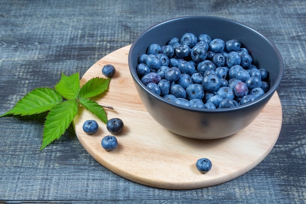 Blueberries in ceramic bowl on wooden cutting board