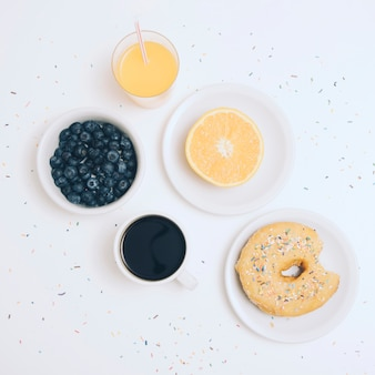 Blueberries; coffee cup; halved orange; juice and donut with colorful sprinkles on white backdrop