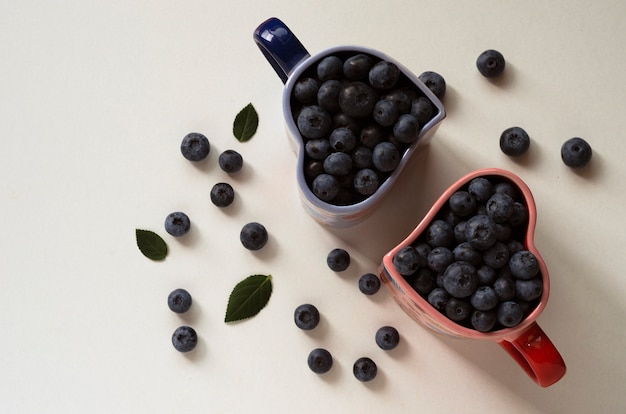Blueberries in cups in the shape of a heart on white