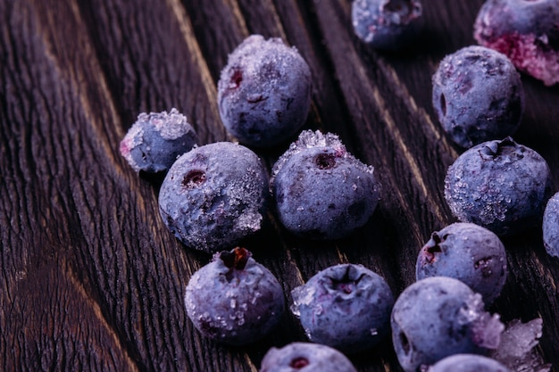 Blueberries frozen on a wooden background