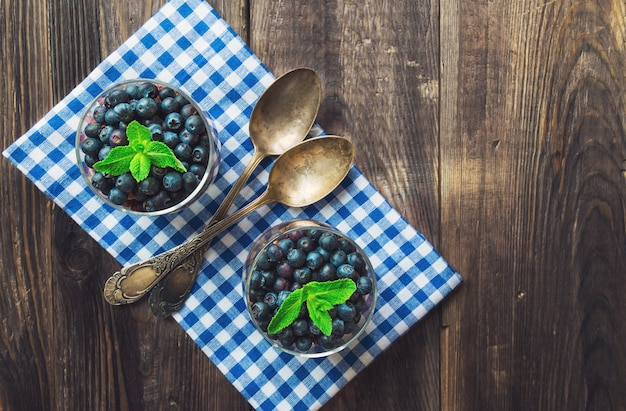 Blueberries in glasses with mint on rustic wooden background. top view.