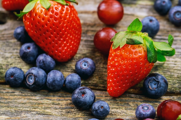 Blueberries grape strawberries fruits on wooden plate on wooden background