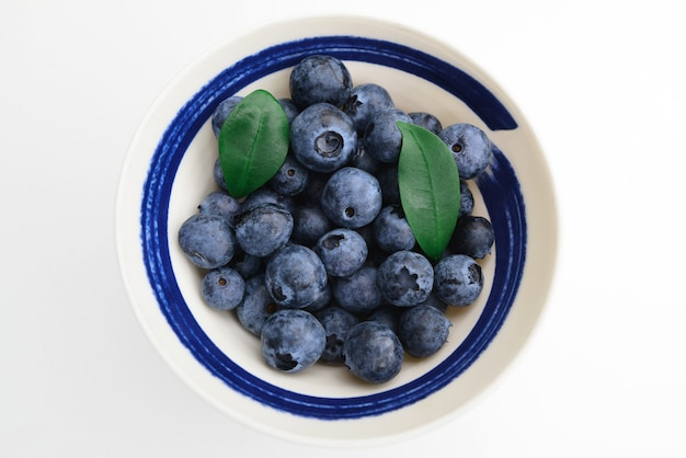 白い背景の上の白いカップのブルーベリー新鮮なブルーベリーのクローズアップビュー上面図青と黒のベリーのコレクション概念的な食品の画像健康的な食品と食事の概念