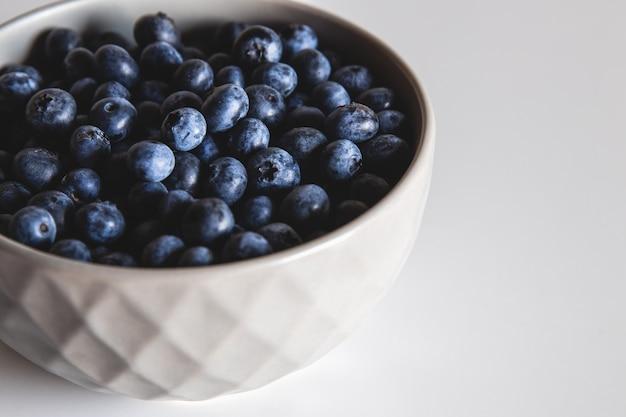 白い表面で隔離のボウルのブルーベリー。健康食品、健康